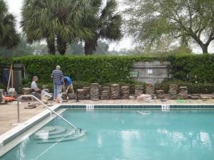 Volunteers helping to repair out pool deck during a volunteer day.